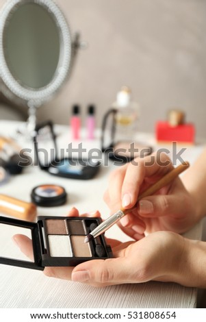 Female hands holding eye shadows, closeup