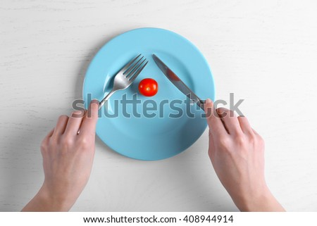 Female hands holding fork and knife on a plate with cherry tomato on white table. - stock photo