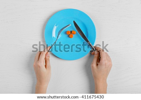 Female hands holding fork and knife on a plate with slices of baby carrots on white table. - stock photo