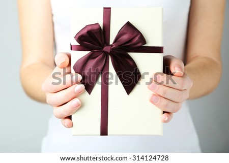 Female hands holding gift box - stock photo