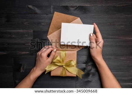 Female hands holding gift card and gift box over the black wooden table - stock photo