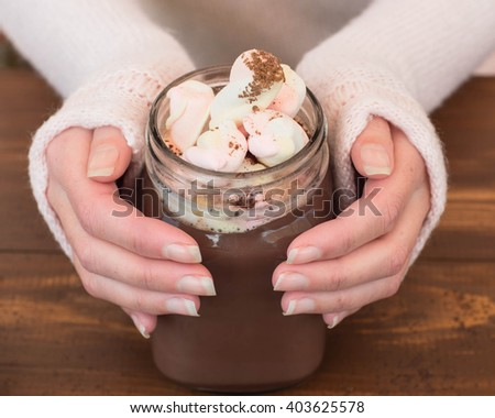 Female hands holding hot chocolate with marshmallows. Top view. - stock photo