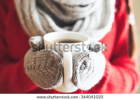 Female hands holding hot mug close up. Woman hands in woolen mittens holding a cup with hot cocoa, tea or coffee. - stock photo
