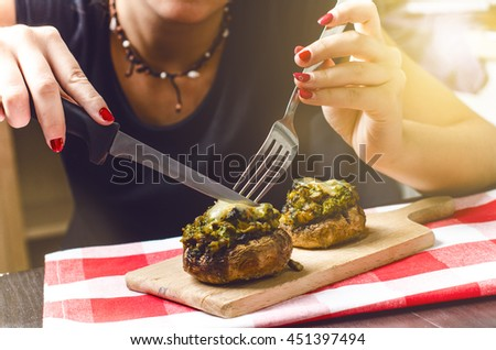 Female hands holding knife and fork and cutting meal. Mushrooms with cheese on a tablecloth. Appetizer. Food background