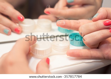 Female hands holding lens, lens case in background, in front of mirror