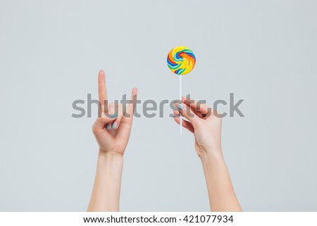 Female hands holding lollipop and showing devil sign isolated on a white background - stock photo