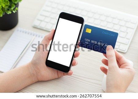 female hands holding phone with isolated screen and a credit card over the desk in the office - stock photo