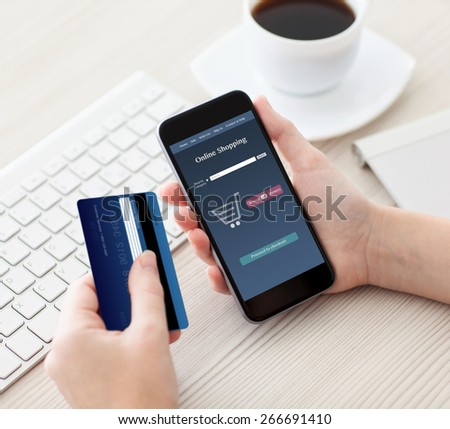 female hands holding phone with online shopping on the screen and a credit card in the office - stock photo