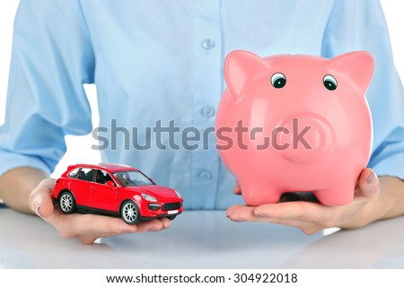 Female hands holding piggy bank and model of car, closeup - stock photo