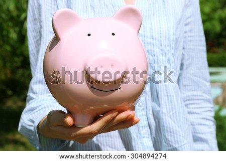 Female hands holding pink piggy bank, outdoors