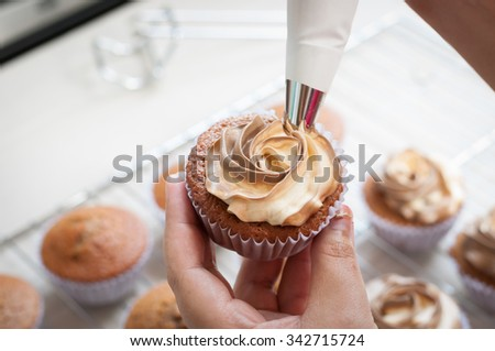 female hands holding piping bag filled with cream cheese and coffee frosting decorating cupcakes - stock photo