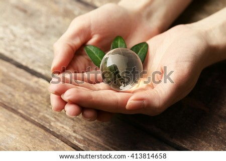 Female hands holding small glass globe on wooden table closeup - stock photo