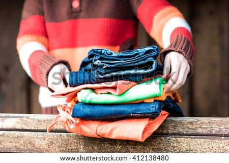 Female hands holding stack of clothing on wooden parapet.