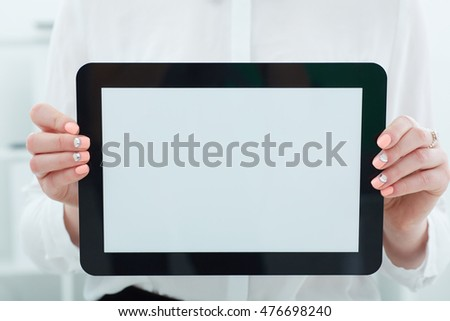 Female hands holding tablet closeup. Tablet with empty space for advertising.