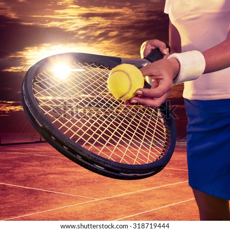 Female hands holding tennis  racket and ball on sky with sun.  - stock photo