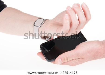 Female hands holding touch phone and smart watch