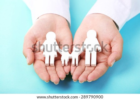 Female hands holding toy family on color background