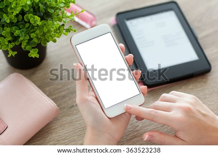 female hands holding white phone with isolated screen and e-rider on the women table