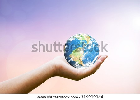 Female hands holding world on blurred sunset background with sun light : The conservation of our planet : Elements of this image furnished by NASA