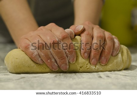 Female hands in flour closeup kneading dough - stock photo