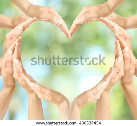 Female hands in heart shape on green nature background