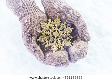 Female hands in knitted mittens with sparkling wonderful snowflake on a white snow background. Winter and Christmas concept.