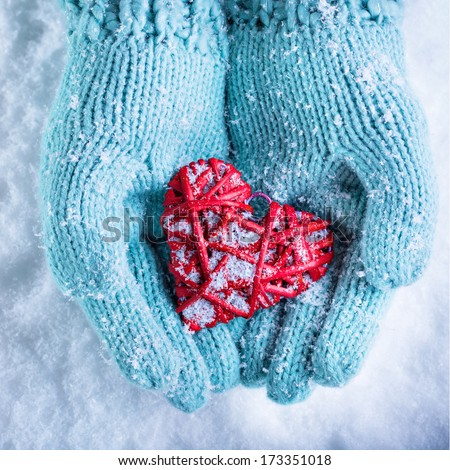 Female hands in light teal knitted mittens with entwined red heart on a white snow background. Love and St. Valentines Day concept.  - stock photo