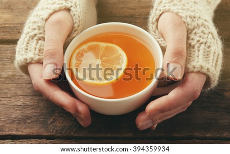 Female hands in mittens holding cup of tea on wooden background - stock photo