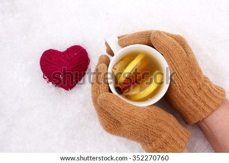 Female hands in mittens holding cup with hot ginger tea. Winter and Christmas time, Valentine day concept. Copy space - stock photo