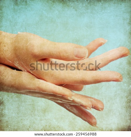 Female hands in moisturizer cream on blue background - stock photo