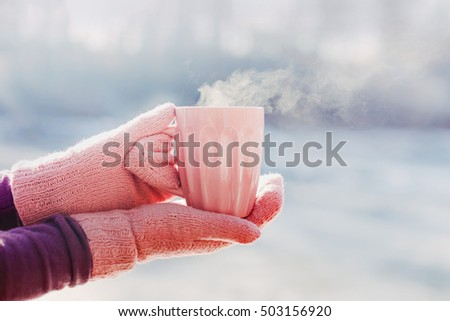 Female hands in pink mittens holding cup with hot tea or coffee. Close up. Winter and Christmas time concept