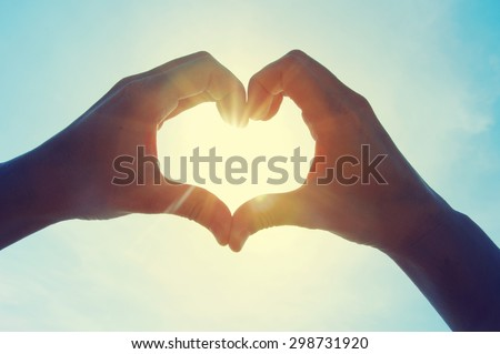 Female hands in the form of heart against the sky pass sun beams. Hands in shape of love heart - stock photo