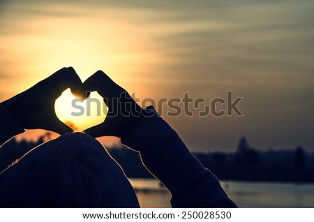 Female hands in the form of heart isolated on the sunrise - stock photo
