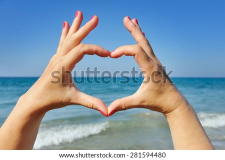 Female hands in the shape of heart on the background sea - stock photo
