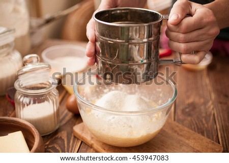 Female hands, ingredients and devices for preparation of cup-cakes on a wooden background. House pastries. Food concept. Flour, eggs, butter, mix for pastries.