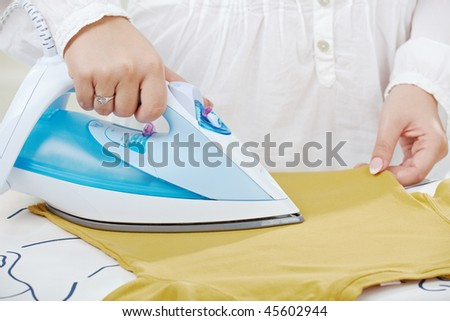 Female hands ironing t-shirt on ironing board.