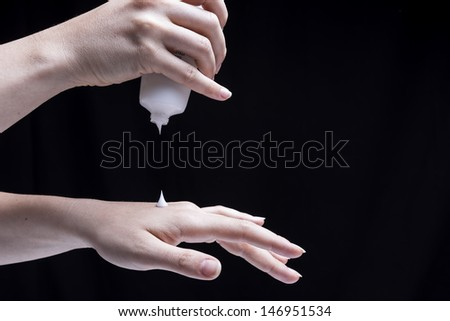 Female hands, isolated on black background, are smearing cream on themselves - stock photo