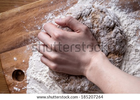 female hands knead the dough for bread - stock photo