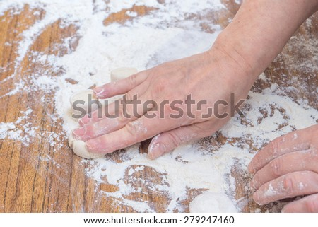 Female hands knead the dough pieces