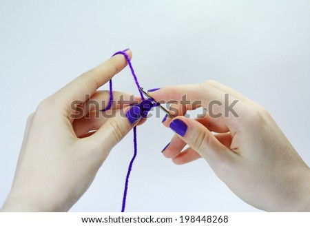 Female hands knitting with violet thread close up - stock photo