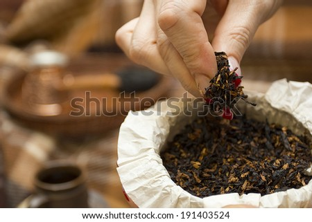 Female hands lifting pipe tobacco. - stock photo