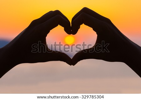 Female hands making a heart shape in the sunset - health, love concept. - stock photo