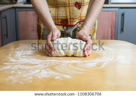 Female hands making dough for pizza or bread while using rolling pin. Baking concept
