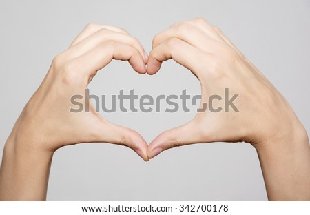 Female hands making shape heart. Symbol of lovers.