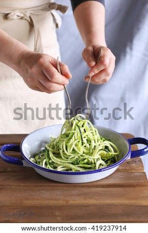 Female hands mixing zucchini noodles with pesto sauce.