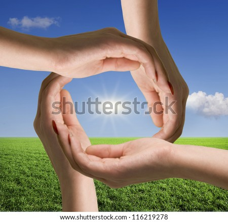 Female hands on a background of green field and sky - stock photo