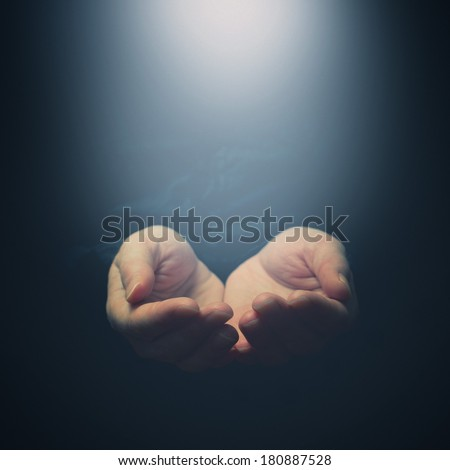 Female hands opening to light. Holding, giving, showing concept. Selective focus on fingers. - stock photo