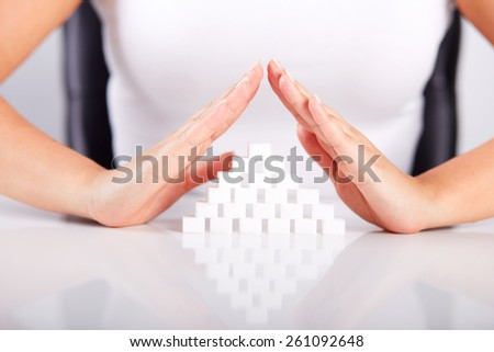 Female hands over a pyramid of sugar cubes - stock photo