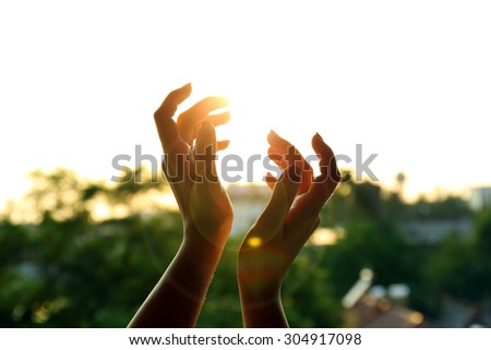 Female hands over sunset sky background - stock photo