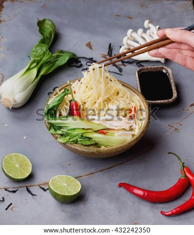 Female hands picking up ingredient from Japanese ramen soup with tofu cheese, noodles, bok choi, mushrooms, seaweed, chili, and lime  served with turquoise chopsticks over metal table.    - stock photo